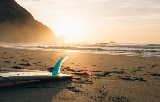Tabla de surf en una playa al atardecer
